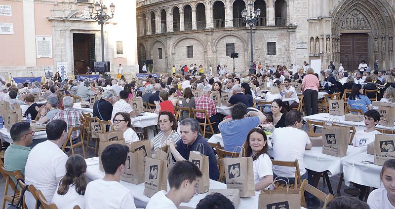 Manos Unidas Valencia llena de comensales la plaza de la Virgen en su Cena del Hambre Personas que iban a restaurantes se unieron al menú solidario: un trozo de pan, una fruta y agua